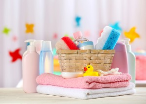 Baby accessories for bathing on table on light background